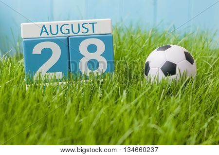 August 28th. Image of august 28 wooden color calendar on green grass lawn background with soccer ball. Summer day. Empty space for text.