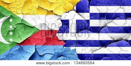 Comoros flag with Greece flag on a grunge cracked wall