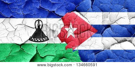 Lesotho flag with cuba flag on a grunge cracked wall