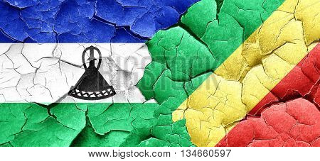 Lesotho flag with congo flag on a grunge cracked wall