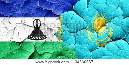 Lesotho flag with Kazakhstan flag on a grunge cracked wall