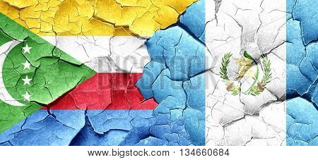 Comoros flag with Guatemala flag on a grunge cracked wall