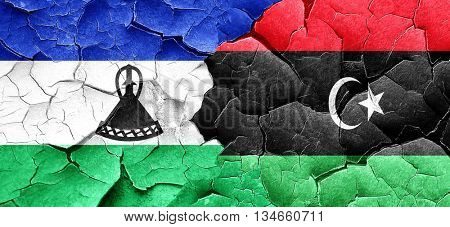 Lesotho flag with Libya flag on a grunge cracked wall