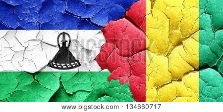 Lesotho flag with Guinea flag on a grunge cracked wall