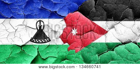 Lesotho flag with Jordan flag on a grunge cracked wall
