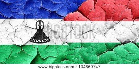Lesotho flag with Hungary flag on a grunge cracked wall
