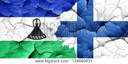 Lesotho flag with Finland flag on a grunge cracked wall