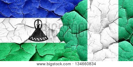 Lesotho flag with Nigeria flag on a grunge cracked wall