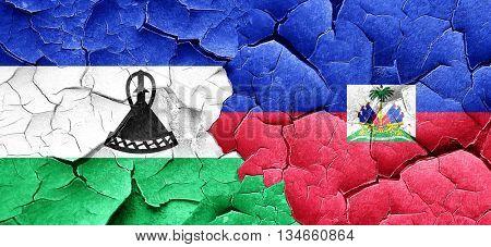 Lesotho flag with Haiti flag on a grunge cracked wall