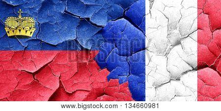Liechtenstein flag with France flag on a grunge cracked wall