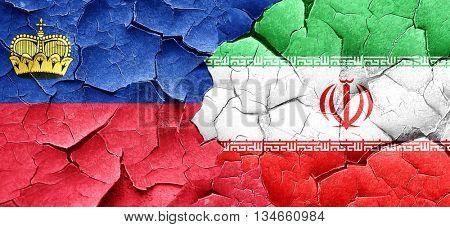 Liechtenstein flag with Iran flag on a grunge cracked wall
