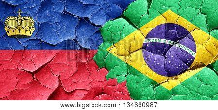 Liechtenstein flag with Brazil flag on a grunge cracked wall