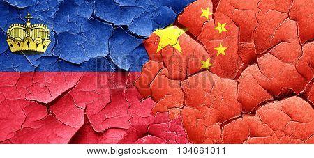 Liechtenstein flag with China flag on a grunge cracked wall