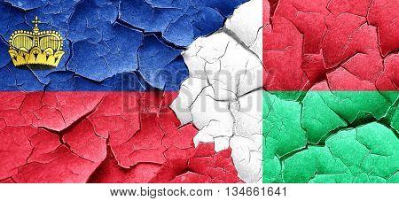 Liechtenstein flag with Madagascar flag on a grunge cracked wall