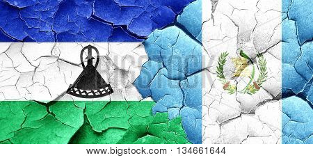 Lesotho flag with Guatemala flag on a grunge cracked wall
