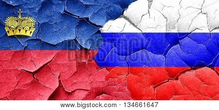 Liechtenstein flag with Russia flag on a grunge cracked wall