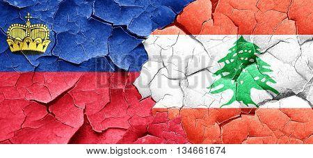 Liechtenstein flag with Lebanon flag on a grunge cracked wall