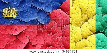 Liechtenstein flag with Guinea flag on a grunge cracked wall