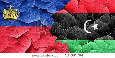 Liechtenstein flag with Libya flag on a grunge cracked wall