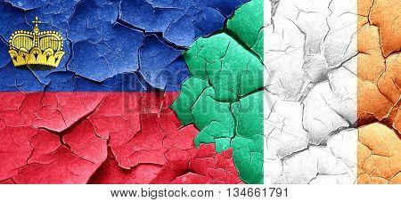Liechtenstein flag with Ireland flag on a grunge cracked wall