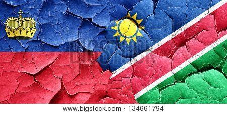 Liechtenstein flag with Namibia flag on a grunge cracked wall