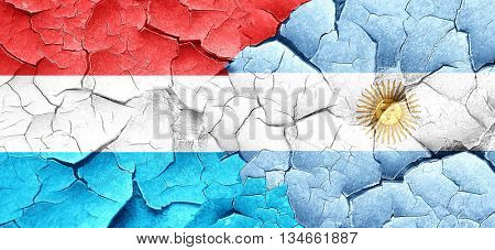 Luxembourg flag with Argentine flag on a grunge cracked wall