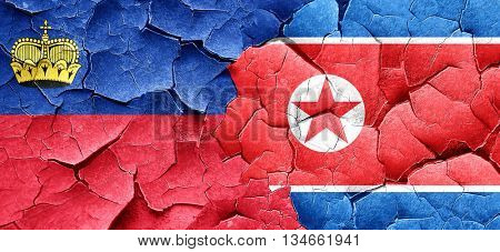 Liechtenstein flag with North Korea flag on a grunge cracked wal