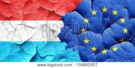 Luxembourg flag with european union flag on a grunge cracked wal