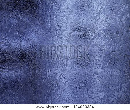 Small frosty patterns on glass in blue tone. Horizontal orientation of a shot