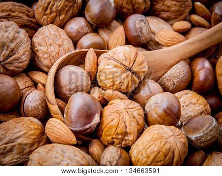 Background With Different Kinds Of Nuts  Walnuts Kernels ,macadamia,hazelnut, And Almond With Wooden