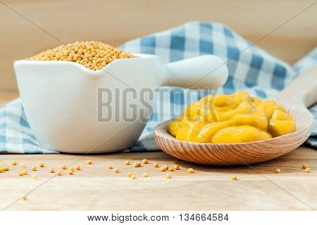 Composition Of Mustard In Wooden Spoon And Mustard Seeds In Ceramic Bowl Setup On Wooden Background.