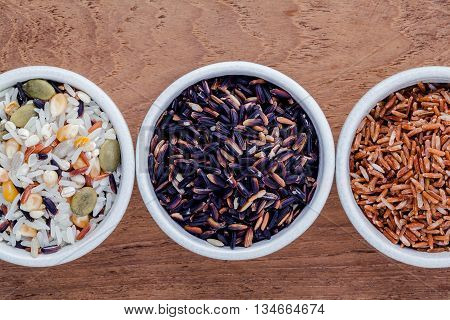Assortment Of Traditional Thai Rice In Ceramic Bowl On Wooden Background. The Supper Food High Fiber