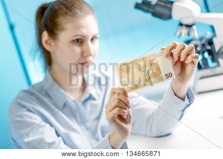 Woman checks the authenticity of Euro banknotes money in a laboratory