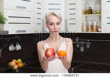 Pretty and Healthy, natural organic raw fresh food concept .Portrait of beautiful girl holding apples and orange fruit her hands in modern kitchen.
