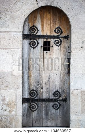 Old wooden faded strong medieval door with metal latches and small grating window on natural background outdoor