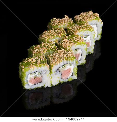 Sushi rolls with salmon cucumber and flying fish roe on black background
