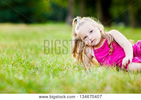 Beautiful little girl in a park during beautiful summer evening