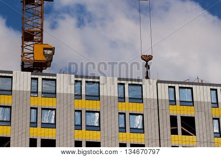 Construction crane and building on a background of sky with clouds