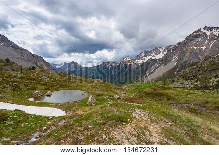 High Altitude Alpine Pond In Extrem Terrain Rocky Landscape Once Covered By Glaciers. Dramatic Storm
