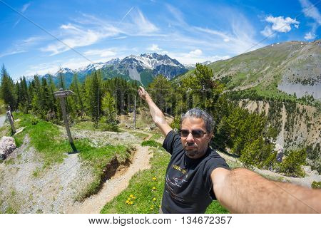 Selfie of adult hiker on top of trail crossing high altitude conifer woodland with snowcapped mountain range in background and moody blue sky. Scenic fisheye distortion.