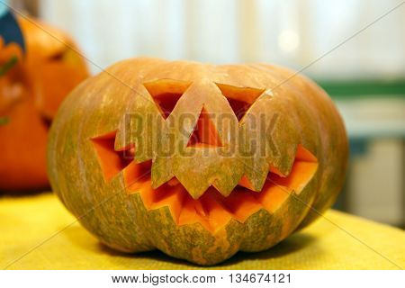 Pumpkin smiling for Halloween. Holiday is celebrated October, eve of all saints Day. Trappings of Halloween in a pumpkin head with a candle inside. Main symbol of holiday is Jack lantern.