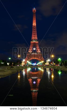 paris; France-June 15 2016 : The Eiffel tower lit up in orange color for soccer Europe championship 2016 in France. The Eiffel tower is one of the most visited monuments in the world.