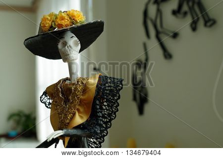 Mexican culture's skeleton with a black hat and yellow flowers on the left side of the frame