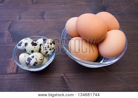 Bowls with quail eggs and chicken on a wooden table