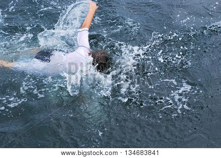 Kid swimming in the river outdoors without any supervision.