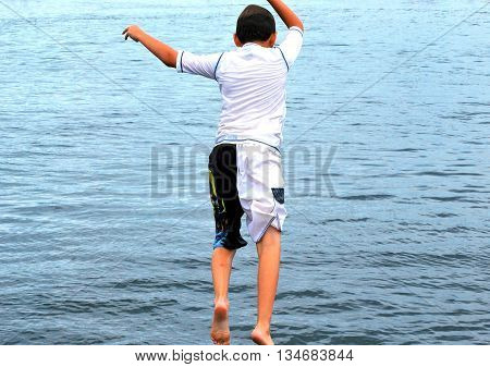 Boy jumping off a pier alone into the lake.