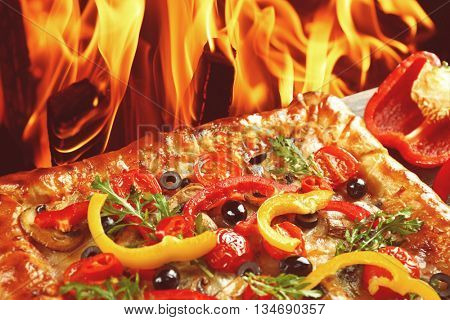 Freshly homemade pizza on fire flame background