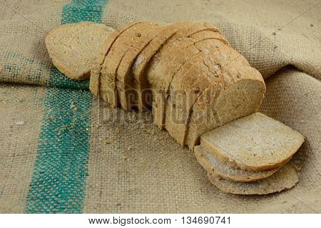 Frozen thawing loaf of sliced bread on burlap