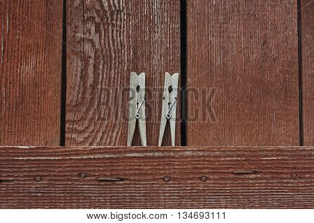 pair lumber clothespeg clothespin on red paint wall close up