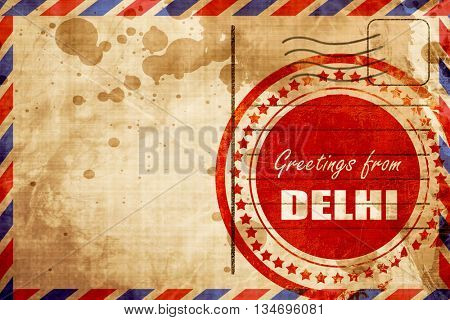 Greetings from delhi, red grunge stamp on an airmail background